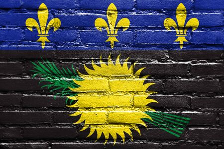 old flag: Flag of Guadeloupe (local), France, painted on brick wall