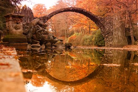 Kromlau、ザクセン、ドイツの Rakotz 橋 (Rakotzbrucke、悪魔の橋)。カラフルな秋、水の橋のリフレクションは、完全な円を作成します。