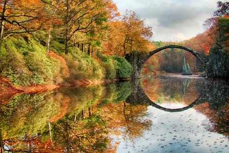 Rakotz Bridge (Rakotzbrucke, Devils Bridge) in Kromlau, Saxony, Germany. Colorful autumn, reflection of the bridge in the water create a full circle Stock Photo