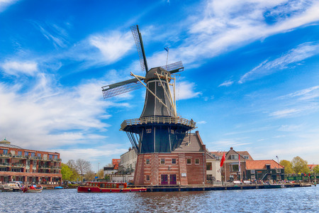 HAARLEM, NETHERLANDS - APR 30, 2017 : Spaarne river with windmill Adriaan. Typical Dutch architecture. View from the boat level.