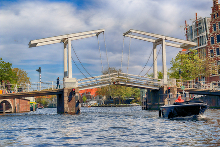 HAARLEM, NETHERLANDS - APR 30, 2017 : Gravestenen drawbridge over Spaarne river. Typical Dutch architecture. View from the boat level.