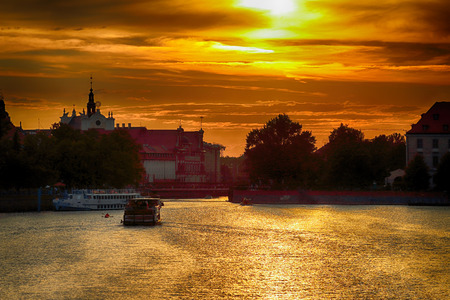 WROCLAW, POLAND - AUGUST 8, 2017: Wroclaw Old Town. Cathedral Island (Ostrow Tumski) is the oldest part of the city. Odra River, boats and historic buildings during the beautiful sunset.