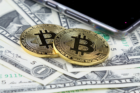 Physical version of Bitcoin (new virtual money) on banknotes of one dollar. Exchange bitcoin cash for a dollar. Conceptual image for worldwide cryptocurrency and digital payment system. Stock Photo