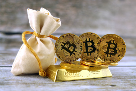 Physical version of Bitcoin, new virtual money. Conceptual image for investors in cryptocurrency and gold. Stock Photo