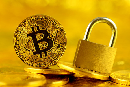 Physical version of Bitcoin (new virtual money) and golden padlock. Conceptual image for money and cryptocurrency security.