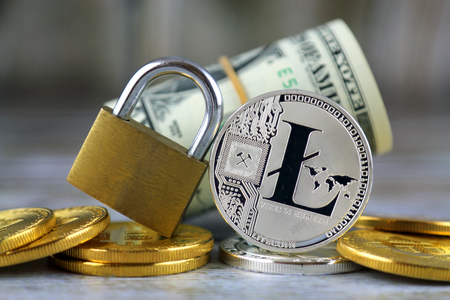 Physical version of Litecoin (new virtual money), golden padlock and banknotes of one dollar. Conceptual image for money and cryptocurrency security. Stock Photo