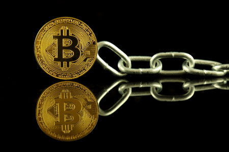 Physical version of Bitcoin (virtual money) and chain. Conceptual image for Blockchain Technology and hard fork (term refers to a situation when a blockchain splits into two separate chains).