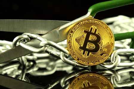 international banking: Physical version of Bitcoin, scissors and chain. Conceptual image for Blockchain Technology and hard fork (term refers to a situation when a blockchain splits into two separate chains).