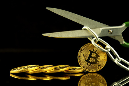 Physical version of Bitcoin, scissors and chain. Conceptual image for Blockchain Technology and hard fork (term refers to a situation when a blockchain splits into two separate chains).