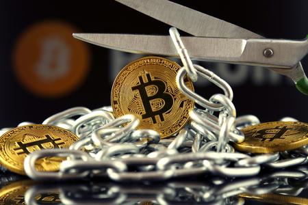 Fysieke versie van Bitcoin, schaar en ketting. Conceptueel beeld voor Blockchain-technologie en harde vork (term verwijst naar een situatie waarin een blockchain zich splitst in twee afzonderlijke ketens).