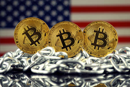 Physical version of Bitcoin (new virtual money), chain and USA Flag. Conceptual image for investors in cryptocurrency and Blockchain Technology in United States.