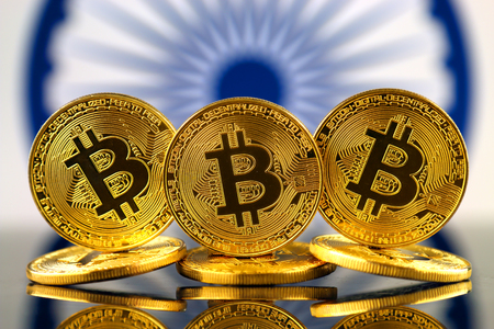 Physical version of Bitcoin (new virtual money) and India Flag. Conceptual image for investors in cryptocurrency and Blockchain Technology in India.