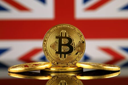 uk money: Physical version of Bitcoin (new virtual money) and UK Flag. Conceptual image for investors in cryptocurrency and Blockchain Technology in United Kingdom. Stock Photo