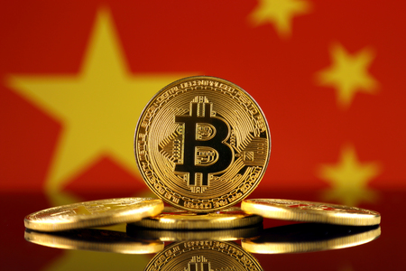 Physical version of Bitcoin (new virtual money) and China Flag. Conceptual image for investors in cryptocurrency and Blockchain Technology in China.