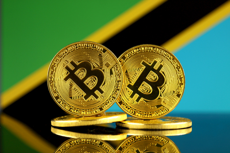 Physical version of Bitcoin and Tanzania Flag. Close up.