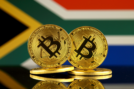 Physical version of Bitcoin and South Africa Flag. Close up. Stock Photo