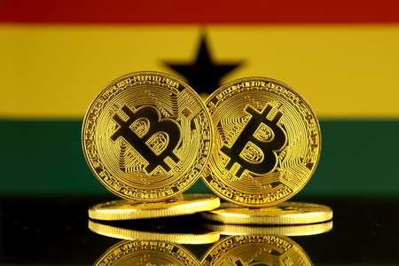 Physical version of Bitcoin and Ghana Flag. Close up.