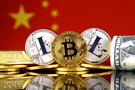 Physical version of Bitcoin, Litecoin, gold, US Dollar and China Flag. Conceptual image for investors in cryptocurrency, gold and dollars. Stock Photo