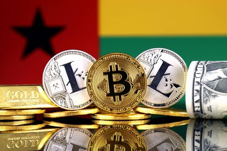 Physical version of Bitcoin, Litecoin, gold, US Dollar and Guinea Bissau Flag. Conceptual image for investors in cryptocurrency, gold and dollars. Stock Photo