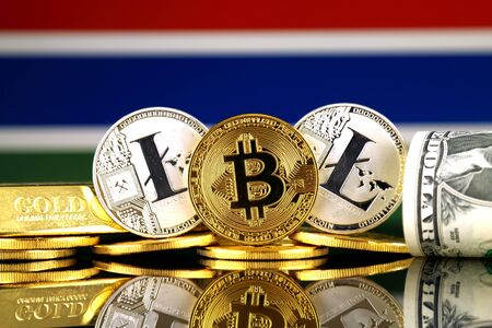 Physical version of Bitcoin, Litecoin, gold, US Dollar and Gambia Flag. Conceptual image for investors in cryptocurrency, gold and dollars.