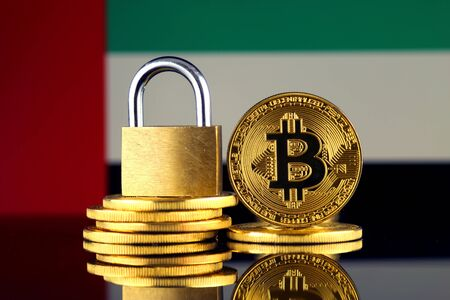 Physical version of Bitcoin, golden padlock and United Arab Emirates Flag. Prohibition of cryptocurrencies, regulations, restrictions or security, protection, privacy.