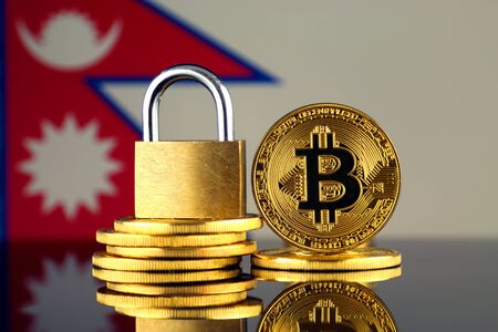 Physical version of Bitcoin, golden padlock and Nepal Flag. Prohibition of cryptocurrencies, regulations, restrictions or security, protection, privacy. Stock Photo