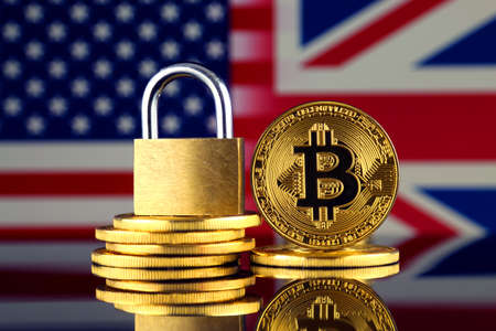 Physical version of Bitcoin, golden padlock, United States and United Kingdom Flag. Prohibition of cryptocurrencies, regulations, restrictions or security, protection, privacy. Stock Photo