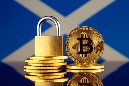 Physical version of Bitcoin, golden padlock and Scotland Flag. Prohibition of cryptocurrencies, regulations, restrictions or security, protection, privacy. Stock Photo