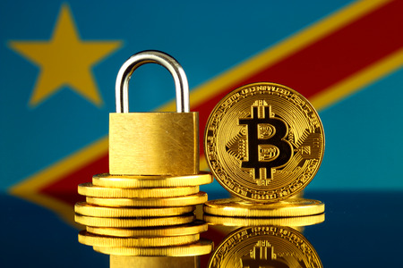 Physical version of Bitcoin, golden padlock and Democratic Republic of the Congo Flag. Prohibition of cryptocurrencies, regulations, restrictions or security, protection, privacy.