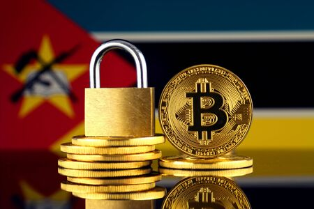 Physical version of Bitcoin, golden padlock and Mozambique Flag. Prohibition of cryptocurrencies, regulations, restrictions or security, protection, privacy.