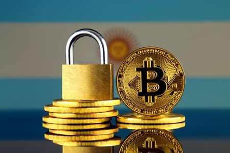 Physical version of Bitcoin, golden padlock and Argentina Flag. Prohibition of cryptocurrencies, regulations, restrictions or security, protection, privacy.
