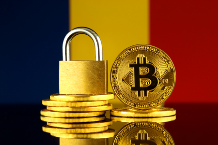 Physical version of Bitcoin, golden padlock and Romania Flag. Prohibition of cryptocurrencies, regulations, restrictions or security, protection, privacy.