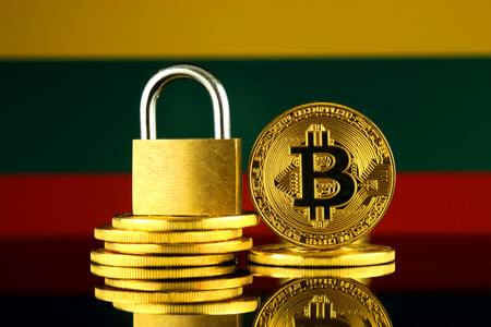 Physical version of Bitcoin, golden padlock and Lithuania Flag. Prohibition of cryptocurrencies, regulations, restrictions or security, protection, privacy. Stock Photo