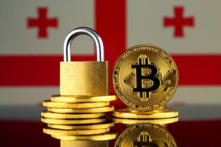 Physical version of Bitcoin, golden padlock and Georgia Flag. Prohibition of cryptocurrencies, regulations, restrictions or security, protection, privacy.