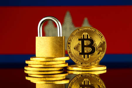 Physical version of Bitcoin, golden padlock and Cambodia Flag. Prohibition of cryptocurrencies, regulations, restrictions or security, protection, privacy. Stock Photo