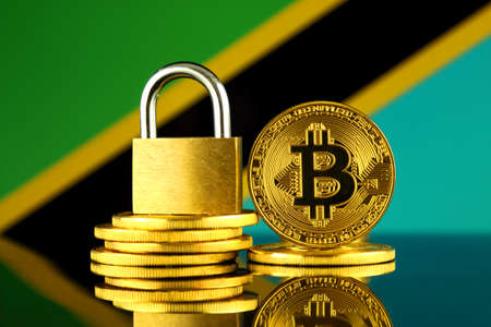 Physical version of Bitcoin, golden padlock and Tanzania Flag. Prohibition of cryptocurrencies, regulations, restrictions or security, protection, privacy. Stok Fotoğraf