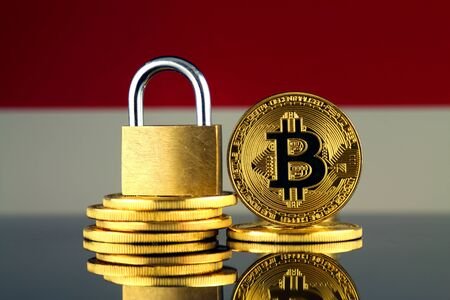 Physical version of Bitcoin, golden padlock and Indonesia Flag. Prohibition of cryptocurrencies, regulations, restrictions or security, protection, privacy.
