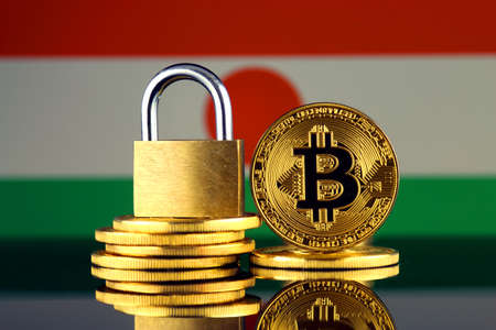 Physical version of Bitcoin, golden padlock and Niger Flag. Prohibition of cryptocurrencies, regulations, restrictions or security, protection, privacy.