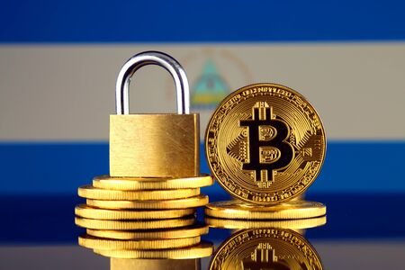 Physical version of Bitcoin, golden padlock and Nicaragua Flag. Prohibition of cryptocurrencies, regulations, restrictions or security, protection, privacy.