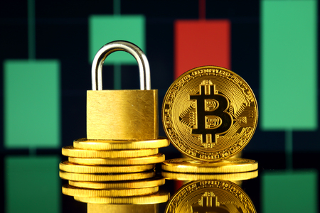 Physical version of Bitcoin and golden padlock. Prohibition of cryptocurrencies, regulations, restrictions or security, protection, privacy. Stock Photo