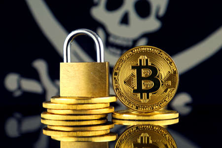 Physical version of Bitcoin, golden padlock and Pirate Flag. Prohibition of cryptocurrencies, regulations, restrictions or security, protection, privacy. Stock Photo