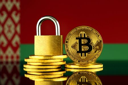 Physical version of Bitcoin, golden padlock and Belarus Flag. Prohibition of cryptocurrencies, regulations, restrictions or security, protection, privacy.