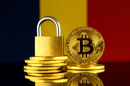 Physical version of Bitcoin, golden padlock and Chad Flag. Prohibition of cryptocurrencies, regulations, restrictions or security, protection, privacy. Stock Photo