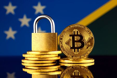 Physical version of Bitcoin, golden padlock and Solomon Islands Flag. Prohibition of cryptocurrencies, regulations, restrictions or security, protection, privacy.