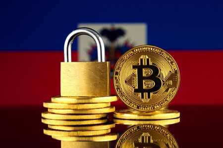 Physical version of Bitcoin, golden padlock and Haiti Flag. Prohibition of cryptocurrencies, regulations, restrictions or security, protection, privacy.