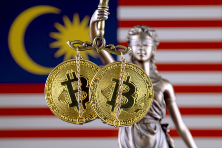 Symbol of law and justice, physical version of Bitcoin and Malaysia Flag. Prohibition of cryptocurrencies, regulations, restrictions or security, protection, privacy. Stock Photo