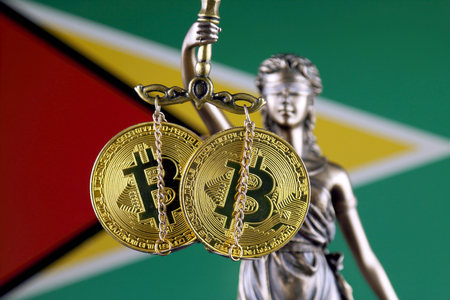 Symbol of law and justice, physical version of Bitcoin and Guyana Flag. Prohibition of cryptocurrencies, regulations, restrictions or security, protection, privacy.
