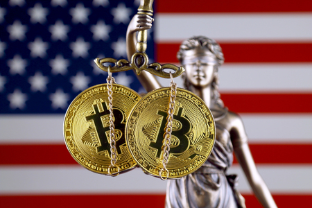 Symbol of law and justice, physical version of Bitcoin and United States Flag. Prohibition of cryptocurrencies, regulations, restrictions or security, protection, privacy. Stock Photo