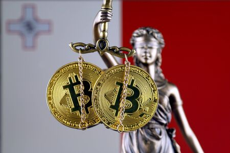 Symbol of law and justice, physical version of Bitcoin and Malta Flag. Prohibition of cryptocurrencies, regulations, restrictions or security, protection, privacy. Zdjęcie Seryjne
