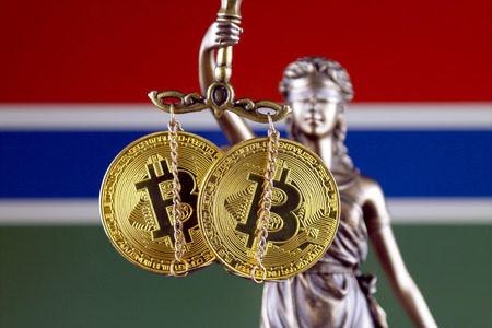 Symbol of law and justice, physical version of Bitcoin and Gambia Flag. Prohibition of cryptocurrencies, regulations, restrictions or security, protection, privacy.